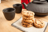 Chocolate biscuits with teapot and mugs, wooden background
