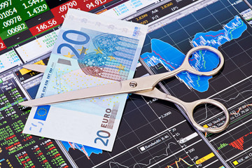 Scissors cutting  euro  banknote. Financial charts and columns o