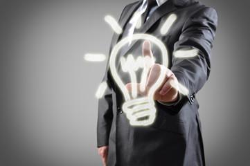 Businessman pressing light bulb button