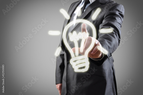 Businessman pressing light bulb button