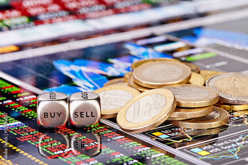 Dices cubes with the words SELL BUY, one-euro coins and a financ
