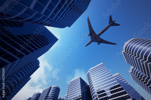 Tuinposter Aan het plafond Business towers with a airplane silhouette