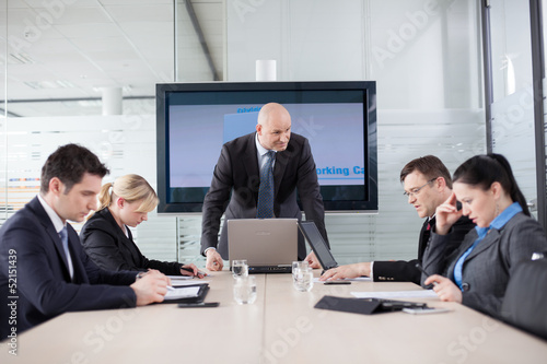 Angry boss at the meeting. Employess are looking down, afraid to