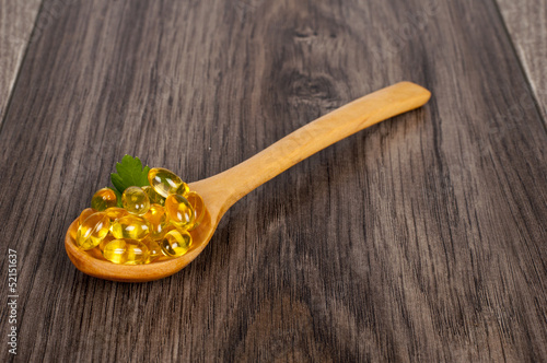 spoon full of tablets on wooden table