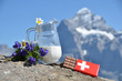 Swiss chocolate and jug of milk against mountain peak. Switzerla