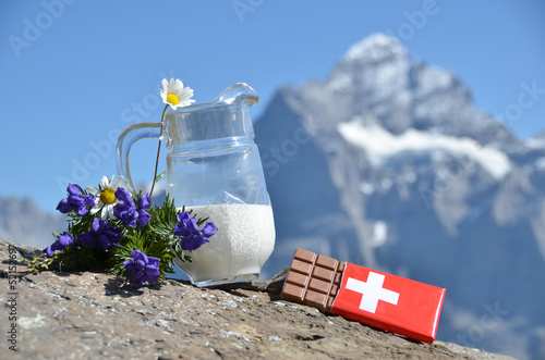Leinwandbild Motiv Swiss chocolate and jug of milk against mountain peak. Switzerla