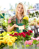 Garden center worker smiling and holding up yellow flower