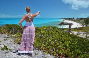 Girl looking along the coastline of Little Exuma, Bahamas