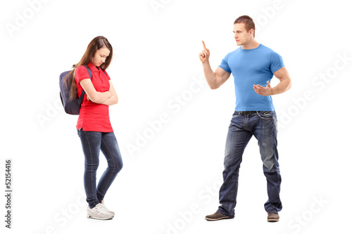 Angry brother pointing with finger and threatening at his sister
