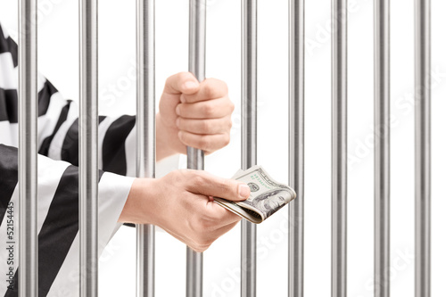 Man in jail holding prison bars and giving bribe