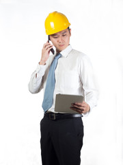 construction supervisor checking on tablet and talking on phone
