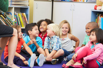 Group of Elementary Pupils In Classroom Listening To Teacher