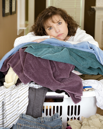 Unhappy  woman resting on messy pile of laundry
