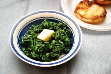 Bowl of Cooked Spinach with a Pad of Butter