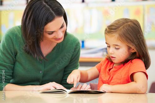 Leinwanddruck Bild Elementary Pupil Reading With Teacher In Classroom