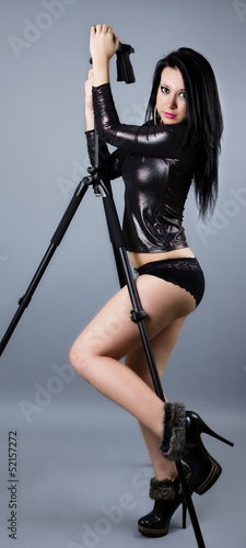 Sexy brunette leaning on tripod