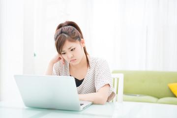 部屋でパソコンを使う女性