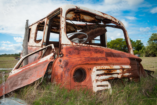 Rusty red and white vehicle wreck