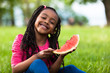 Outdoor portrait of a cute young black little girl eating waterm