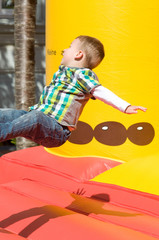 Kleiner Junge spielt auf der Hüpfburg