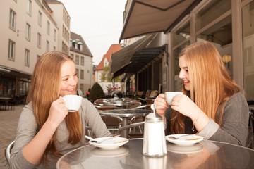 Zwei Freundinnen trinken Kaffee / Tee in der Stadt
