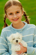 Lovely girl with cute puppy in the garden