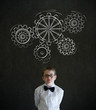 Boy dressed as business man chalk turning gear cogs