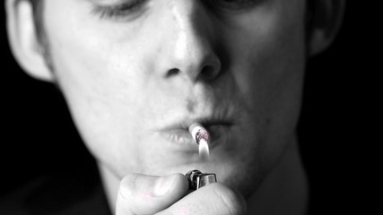Man lighting up a cigarette in black and white