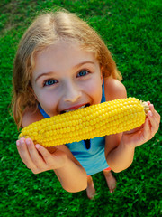 Child in the garden - lovely girl eating corn on the cob