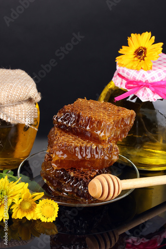 Jars of honey and honeycomb on black background