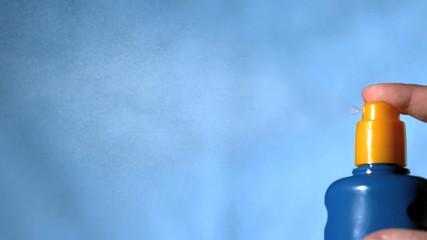 Hand spraying sun cream on blue background