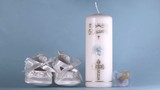 Baby shoes falling beside baptism candle on blue background