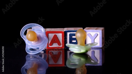 Pacifiers falling in front of blocks spelling baby