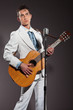 Retro rock and roll singer with guitar wearing white suit. Studi