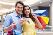 Beautiful couple showing credit card in the shopping mall