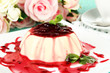 Panna Cotta with raspberry sauce, on color wooden background