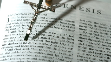 Rosary beads falling onto the book of genesis