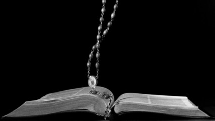 Rosary beads falling onto open bible