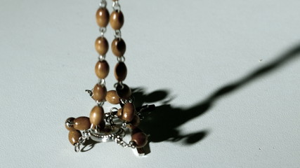 Rosary beads casting a shadow and then falling on white surface