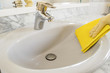 gray sink cleaning with yellow gloves