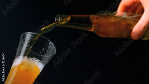 Hand pouring bottle of beer into glass on black background