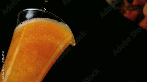 Beer pouring into glass on black background low angle view