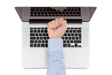 Top view of modern retina laptop with a man's fist
