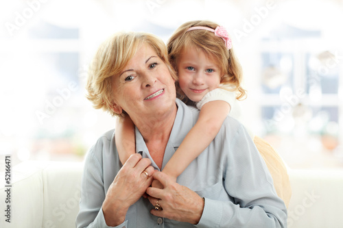 Smiling young girl hugging her grandmother