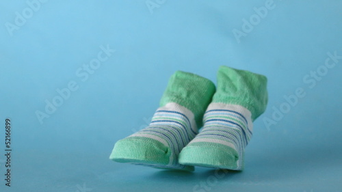 Green slippers falling on blue background