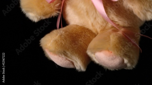Cute teddy bear falling on black background close up