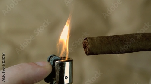 Hand lighting a cigar on beige background