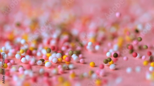 Sprinkles falling on pink surface