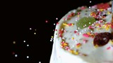 Colourful sprinkles pouring onto iced cake with candy