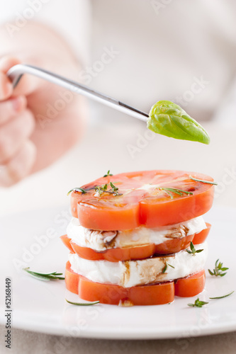 Hand serving a basil leaf on mozzarella and tomato slices close-